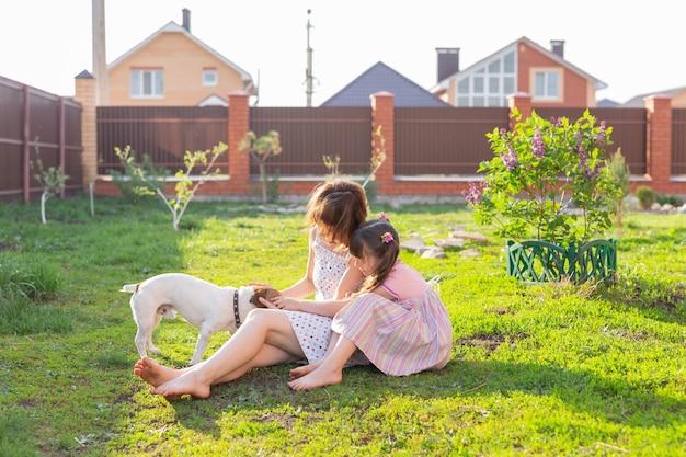Petite fille en robe rose avec sa mère et chien jack russell terrier sur la cour