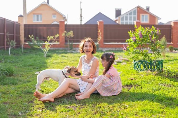 Petite fille en robe rose avec sa mère et jack russell terrier chien sur la cour assis sur l'herbe