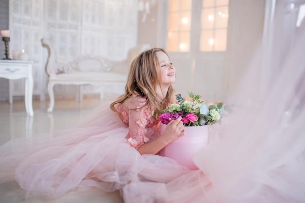 Petite fille en robe rose tient la boîte avec des roses assis sur le sol dans une chambre de luxe