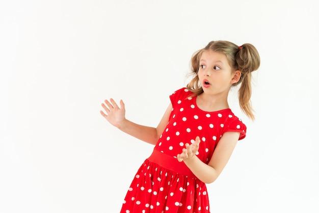 Une petite fille en robe rouge est surprise par votre annonce.