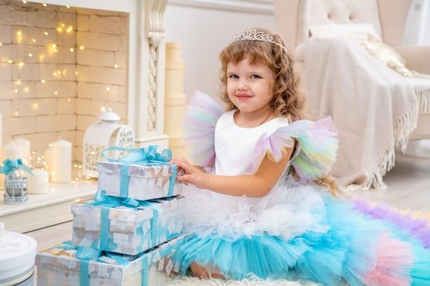 Petite fille en robe de soirée décoration énorme arbre de noël blanc