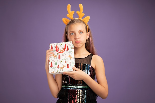 Petite fille en robe de soirée pailletée et bandeau drôle avec des cornes de cerf tenant un sac en papier de noël avec des cadeaux regardant la caméra mécontente debout sur fond violet