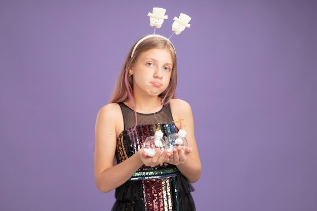 Petite fille en robe de soirée scintillante et bandeau drôle tenant des boules de noël regardant la caméra mécontente debout sur fond violet