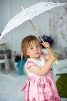 Petite fille en robe tenant un parapluie