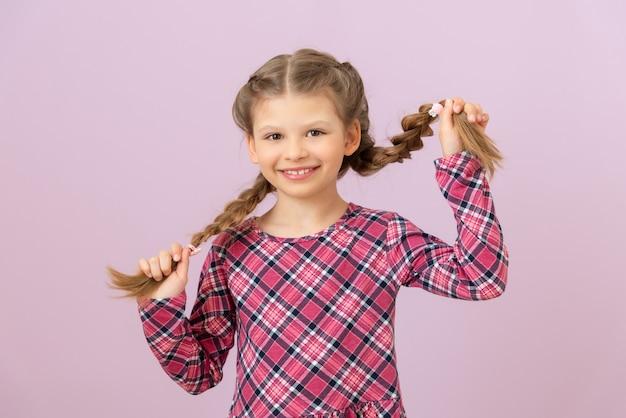 Une petite fille en robe tient ses tresses avec ses mains et sourit.