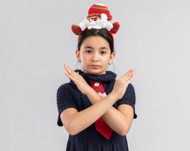 Petite fille en robe en tricot portant une cravate rouge avec jante de noël drôle sur la tête à la recherche avec un visage sérieux faisant le geste d'arrêt en traversant les mains
