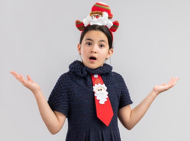 Petite fille en robe en tricot portant une cravate rouge avec jante de noël drôle sur la tête à la surprise avec les bras levés