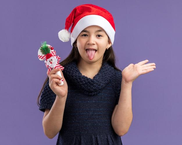 Petite fille en robe tricotée portant un bonnet de noel tenant une canne en bonbon de noël heureuse et joyeuse qui sort la langue debout sur un mur violet