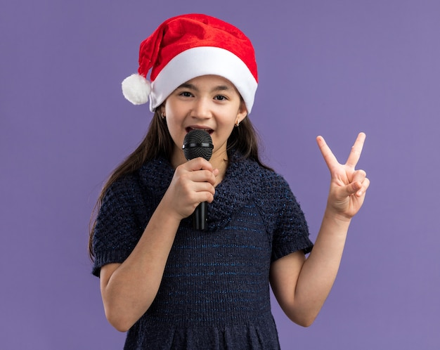 Petite fille en robe tricotée portant un bonnet de noel tenant un microphone chantant célébrant la fête de noël heureuse et positive montrant un signe v debout sur un mur violet