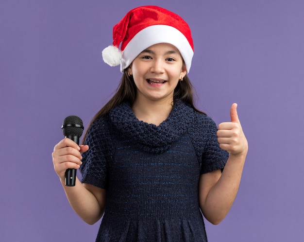 Petite fille en robe tricotée portant un bonnet de noel tenant un microphone heureux et positif montrant les pouces vers le haut debout sur un mur violet