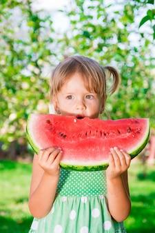 Petite fille en robe verte, manger une grosse tranche de pastèque dans le parc. heure d'été. heureux. joie.