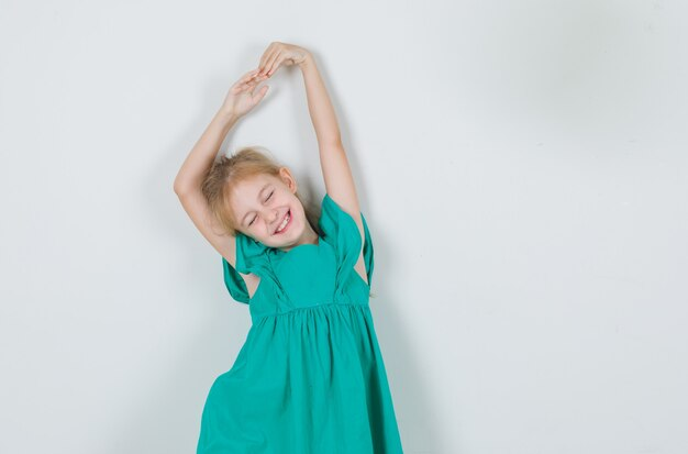 Petite fille en robe verte qui s'étend les bras avec les yeux fermés et à la joyeuse
