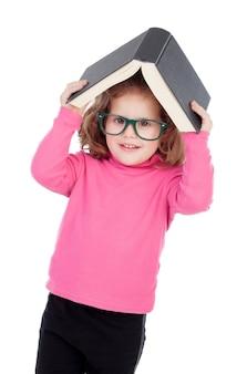 Petite fille en rose avec des lunettes et un livre sur la tête