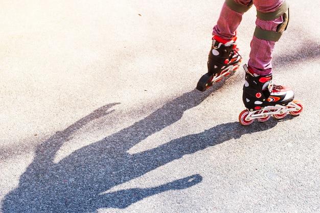Une petite fille roule sur des rouleaux rouges sur l'asphalte