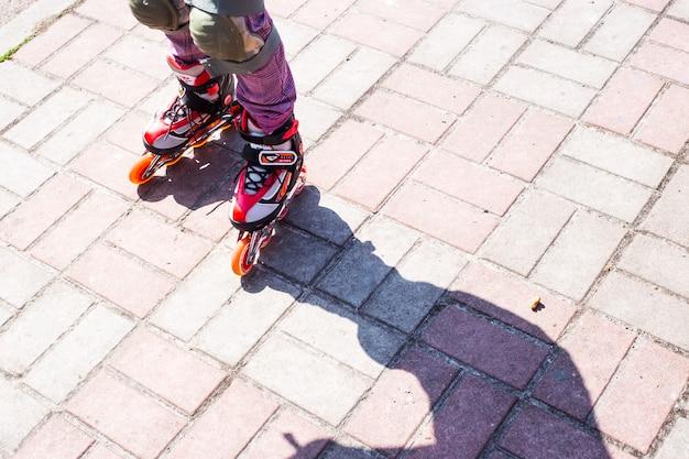 Une petite fille roule sur des rouleaux rouges sur le trottoir
