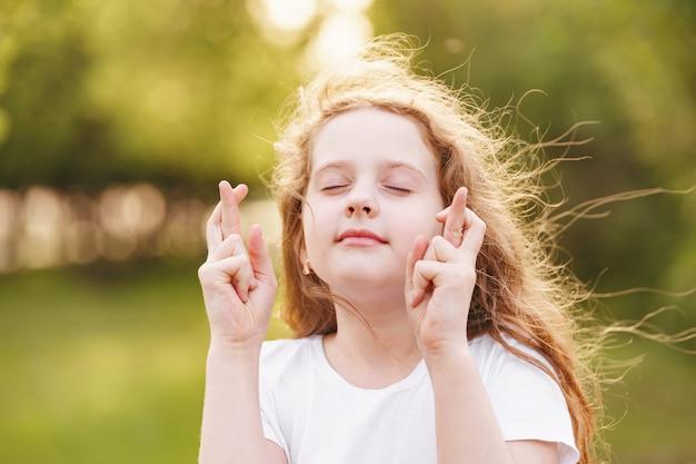 Petite fille rousse fait un vœu désirable à l'extérieur.