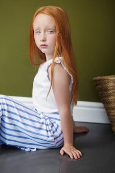 Petite fille rousse avec un panier de fleurs posant sur fond olive. portrait de printemps d'une fille rousse aux yeux bleus. cheveux couleur de feu, adolescente norvégienne