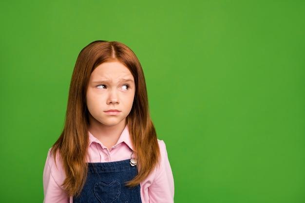 Petite fille rousse posant contre le mur vert