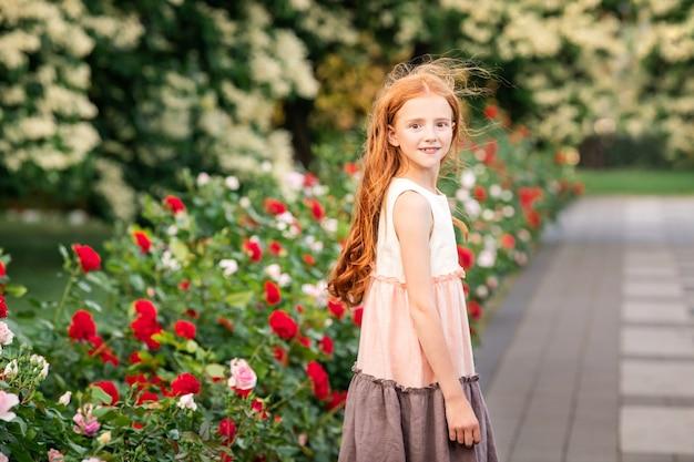 Petite fille rousse reniflant une rose dans un jardin fleuri en été