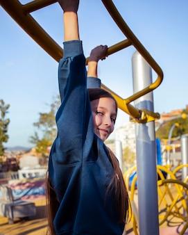 Petite fille s'amusant sur l'aire de jeux à l'extérieur