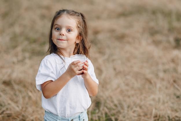 Petite fille s'amusant au pique-nique, pizza, boissons, été et pelouse