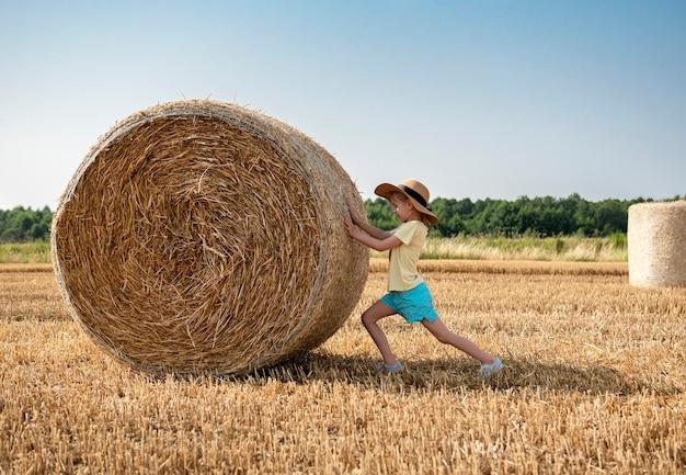 Petite fille s'amusant dans un champ de blé un jour d'été. enfant jouant au champ de balles de foin pendant la récolte.