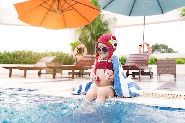 Petite fille s'amusant dans la piscine. vacances d'été et concept de vacances