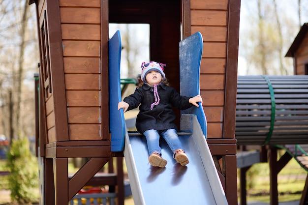 Petite fille s'amuser sur l'aire de jeux extérieure / sur toboggan