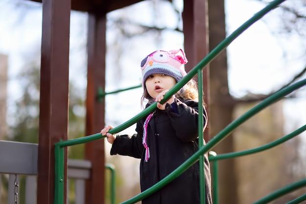 Petite fille s'amuser sur une aire de jeux en plein air au printemps ou en automne