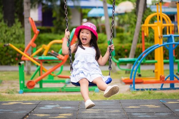 Petite fille s'amuser avec balançoire dans le parc.