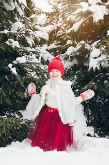 Petite fille s'amuser dans la forêt d'hiver