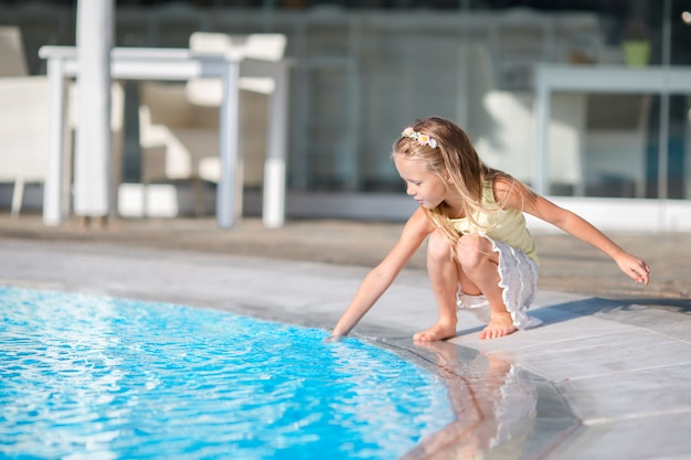 Petite fille s'amuser avec une éclaboussure près de la piscine