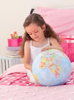 Petite fille s'amuser avec un globe terrestre