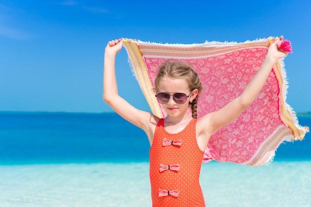 Petite fille s'amuser avec un paréo de plage en vacances tropicales