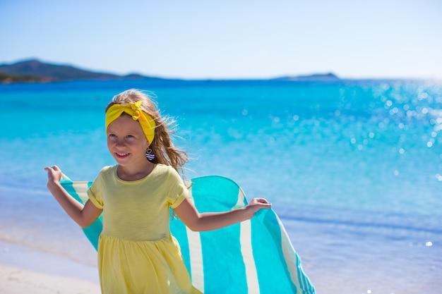 Petite fille s'amuser avec une serviette de plage pendant des vacances tropicales