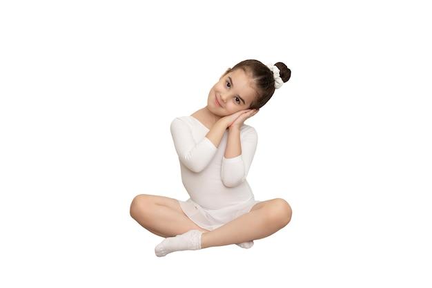 La petite fille s'assied dans un maillot de bain de danse blanc