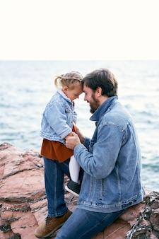 La petite fille s'assied sur les pieds de papa inclinant son front à son front papa s'assied sur des pierres contre le