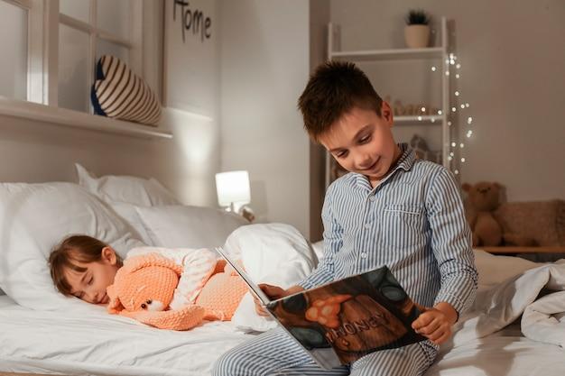 Petite fille s'endormir pendant que son frère lit l'histoire du coucher à la maison