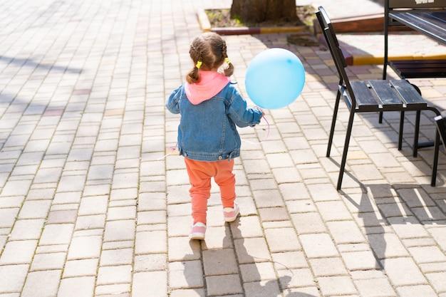 La petite fille s'enfuit de ses parents avec un ballon gonflable à la main.
