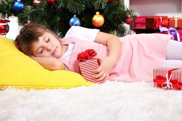 La petite fille s'est endormie avec un cadeau dans les mains dans une pièce décorée de façon festive