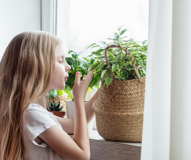 Petite fille s'occupant des plantes d'intérieur à la maison