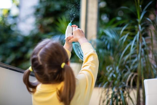 Une petite fille s'occupe des fleurs du balcon et les rafraîchit avec un vaporisateur.