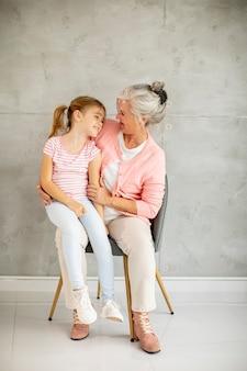 Petite fille avec sa grand-mère assise dans une chaise près du mur gris