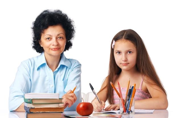 Petite-fille avec sa grand-mère assise sous la table avec des livres vous regardant