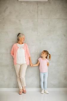 Petite fille avec sa grand-mère debout près du mur gris