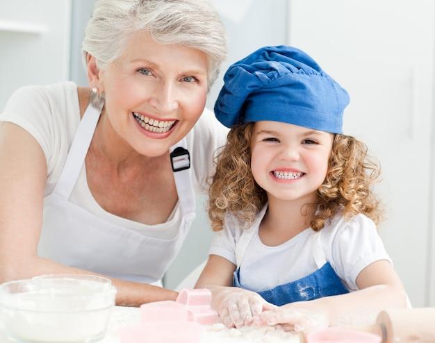 Une petite fille avec sa grand-mère en regardant la caméra