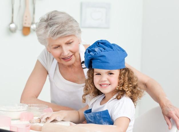 Une petite fille avec sa grand-mère regardant la caméra
