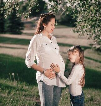 Petite fille et sa maman enceinte heureuse lors d'une promenade dans le parc d'été