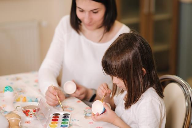 Petite fille avec sa maman se préparant pour pâques et imprimer des oeufs, ils sont assis près de la table et ont
