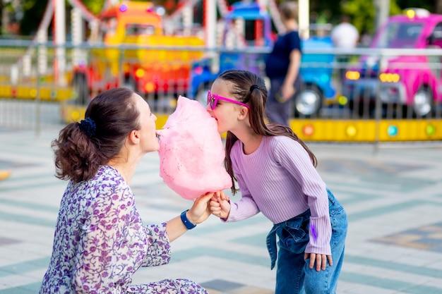 Une petite fille avec sa mère dans un parc d'attractions en été mangeant de la barbe à papa et des glaces près des manèges, s'amusant et riant, le concept des week-ends en famille et des vacances scolaires